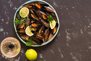 Mussels in wine sauce on a black concrete background, a glass of wine, lime. Top view, copy space. Mediterranean food.