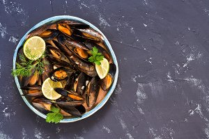 Boiled mussels in wine sauce on grey concrete background. Top view, copy space.