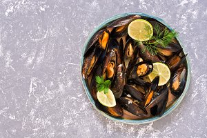 Shellfish mussels in a plate with slices of lemon on a gray background. Top view, space for text.