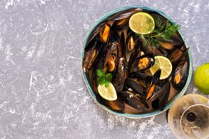 Mussels in wine sauce with lemon and greens on a gray background, a glass of wine, lime. Top view, copy space.