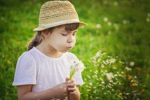 girl blowing dandelions in the air.