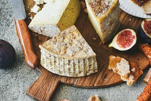 Cheese assortment, figs, honey, fresh bread and nuts, square crop