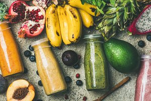 Colorful smoothies in bottles with fresh tropical fruit, square crop