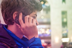 young teenager with phone in the jacket close up portrait in the city