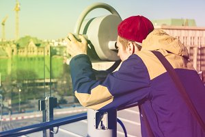 young man looking through binoculars at the city panorama at the summer sunny day