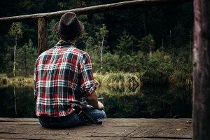 hipster traveler sitting at lake