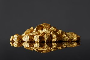 Mound of gold nuggets on a black reflective surface background