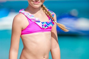 Little happy girl enjoy vacation near outdoor swimming pool