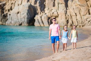 Family of dad and kids on white sandy beach