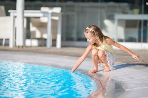 Little girl having fun with a splash near swimming pool