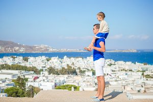 Happy father and little adorable girl in Mykonos during summer greek vacation