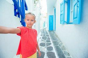 Adorable girl taking self portrait outdoors in greek village