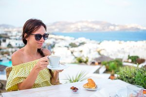 Woman drinking hot coffee on luxury hotel terrace with sea view at resort restaurant.