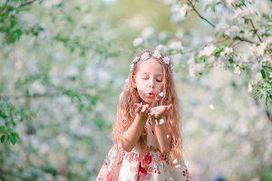 Adorable little girl in blooming cherry tree garden on spring day