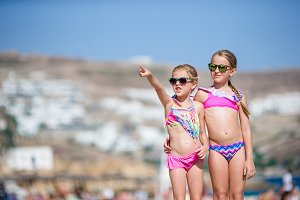 Adorable little girls having fun during beach vacation.