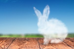 Easter bunny from a cloud on a wooden table on a sky background