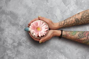 A cup of tea and a gerbera in the hands of a woman on a gray concrete background