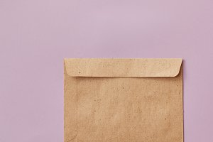 Brown craft envelope isolated on pink background