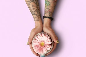 A woman with a tattoo is holding a cup with a gerbera on a pink background.