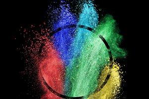 Splash of colorful powder into circle frame over black background.