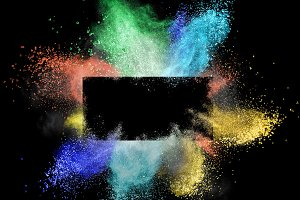 Launched colorful powder around a rectangular frame isolated on black background