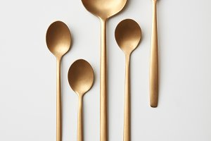 Set of golden spoons on a gray background