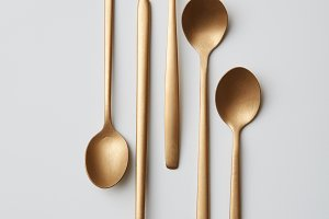 Kitchen set of different golden spoons on a gray background