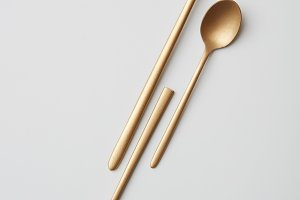 Two small and one big metal spoons isolated on a gray background