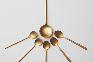 Composition of golden spoons on a gray background