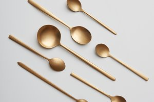 Composition made of golden spoons on a gray background ,.