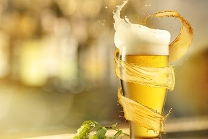 A cold glass of beer with a splash and with a hops on a wooden background