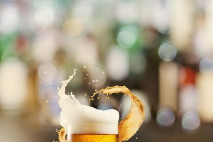 A cold glass of beer and a splash around on a blurred bar counter background