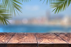 wooden table or wooden mock up with palm trees against the background of a blurry city