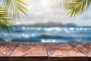Beach blurred background with palm leaves background with vintage old wood table