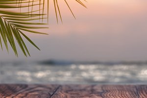 nature background of coconut palm tree on tropical beach sunset with of wood table