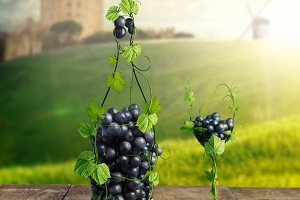 Bottle of Wine and a glass made by of grape leaves and a bunch of grapes on a wooden background