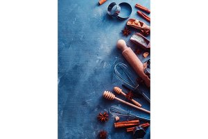 Baking tools and ingredients from above. Cooking concept with wooden scoops, whisks, cookie cutters, sugar, flour, eggs, anise stars and cinnamon on a modern concrete background with copy space