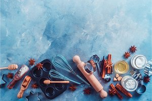 Making pastry concept with baking tools and ingredients on a modern concrete background with copy space. Wooden scoops, whisks, cookie cutters, muffin tin, sugar, flour, anise stars from above.