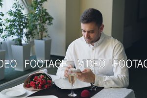 Well-dressed angry young man is waiting for his girlfriend in restaurant, using smartphone, opening jewelry box and looking at ring then leaving, flowers left on table.