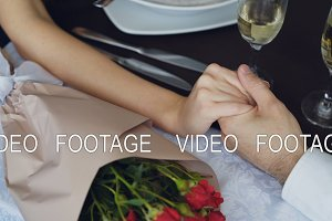 Close-up shot of male hand holding and squeezing female hand on table with champagne glasses and flowers. Romantic relationship, love and fine dining concept.