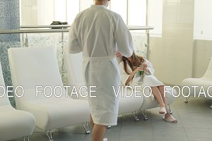 Pretty girl in white bathrobe is relaxing in day spa when her boyfriend is coming and sitting beside her. Young lovers are talking, kissing and drinking cocktails.