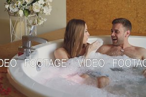 Pretty cheerful girl is blowing soap foam and having fun with her bearded fience in hot tub in day spa. Young people are laughing, enjoying weekend and talking.
