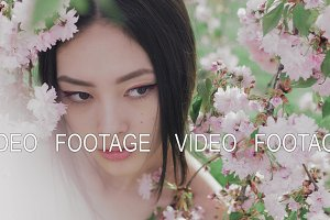 Portrait of a beautiful asian girl outdoors against spring blossom tree.