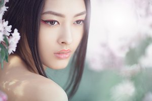Portrait of a beautiful fantasy asian girl outdoors against natural spring flower background.
