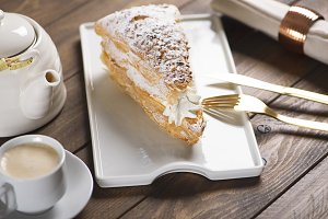 Delicious breakfast of sweet puff pastry with cream on brown wooden table. Horizontal shoot. Food