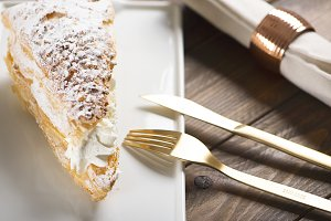 Close-up of delicious breakfast of sweet puff pastry with cream on brown wooden table. Horizontal shoot. Food