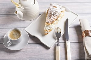 Close-up of delicious breakfast of coffee with sweet puff pastry with cream on wooden table. Horizontal shoot. Food
