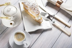 Delicious breakfast of coffee with puff pastry with cream on wooden table. Horizontal shoot. Food