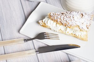 Delicious breakfast of coffee with puff pastry with cream. Vertical shoot. Food