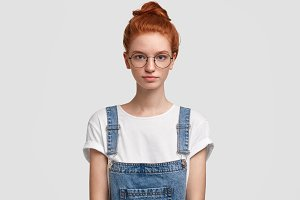 Serious red haired female student poses at camera, wears round spectacles and denim overalls, looks self assured, has freckled skin, isolated on white background. Ginger teenage girl in studio